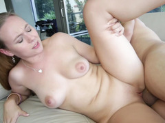 A cute girl that has a shaved pussy is riding dick on the sofa