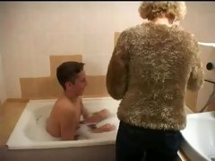 More experienced lady gives young-looking fella bath