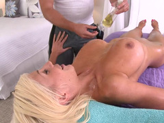 Blonde with large boobs is on the massage table, with no clothes on