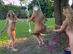 Three girls are playing around naked in the garden in a threesome