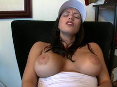 A bimbo with huge hooters and a sexy smile is playing with her cunt