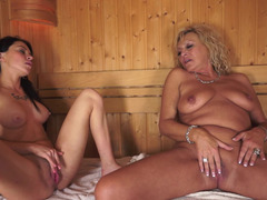 A granny takes care of a hot little brunette in the sauna