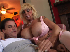 A granny that has huge saggy tits is getting cum over her body