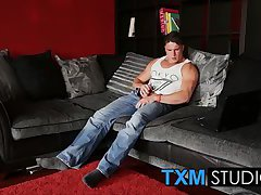 Muscular hunk Harry Coniston masturbates in the living room
