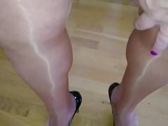 Crossdresser in shiny pantyhose, skirt and high heels