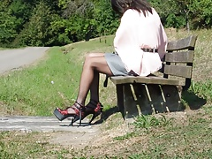 Dildofucking on a park bench near road