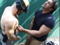 Bearded homo wearing helmet fucks some guy's butt from behind outdoors