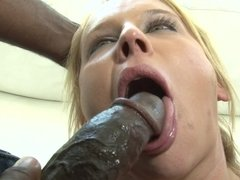 A blonde that has a lovely smile is getting black cocks in her holes