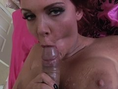 A girl with large tits and red hair is taking care of a big pecker