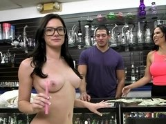 Two women party with a dude in a threesome in a store with a dildo