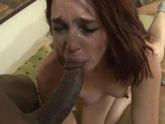 A redhead receives a big dark cock in the interracial video