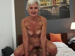 A nasty old short haired granny is sucking a big hard pecker