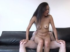A brunette that has small tits is riding a large dude on the sofa