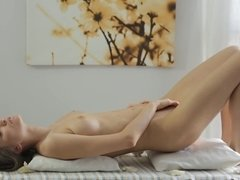 A brunette gets naked on the massage table and massages her cunt