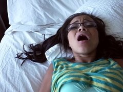 A hot thing with glasses is giving a blow job on the bed