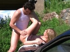A blonde is getting her pussy rammed on the hood of a car