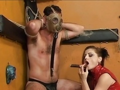 Sexy domme in red dress burns minion with smoking cigarette in dungeon