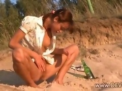 Nasty Natasha playing with bottle on the hot sand outdoors