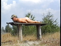 Wanking on a wooden  table on a hill
