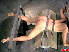 tied black victim in pillory gets spanked