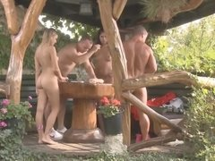 Two blokes and two young babes are having fun in a backyard