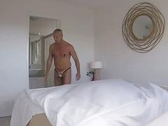 Dirty room service guy makes a bed in his fetish clothes